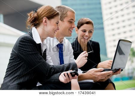 Three business people looking at a laptop computer