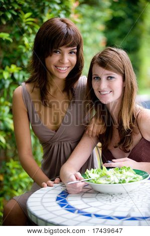 Two young attractive women having lunch together outside