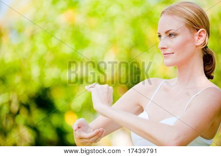 A slim tall woman doing tai chi outside