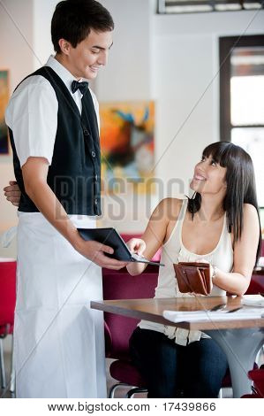 A young and attractive woman paying the bill in a restaurant