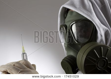 doctor with a gas mask holding medical syringe with needle