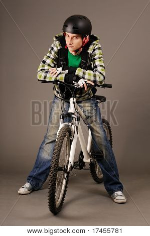 The young male bicyclist with bicycle on grey, studio shot.