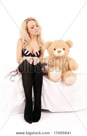 picture of sitting on a bed beautiful girl with a toy bear over white