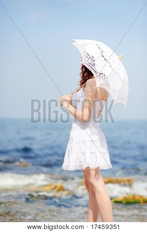 girl in white dress with umbrella on a beach