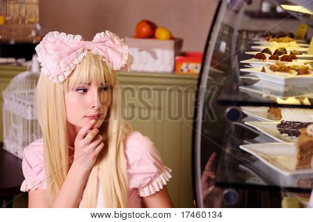 Young beautiful woman looking at cakes.