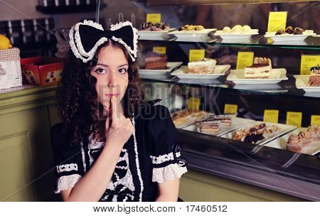 Young beautiful woman with cakes in cafe.