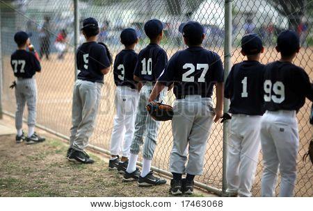 Baseball Players Watching Baseball Game Along Fence With High DOF