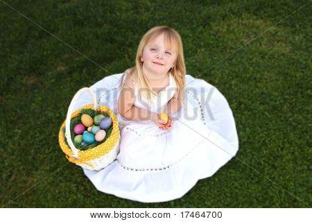 Little Girl Wearing a White Dress Holding Easter Eggs on Green Grass Outdoors