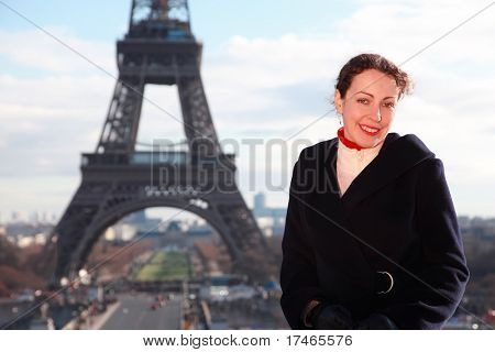 beautiful young woman smiling, view of Eiffel Tower at winter, vertical