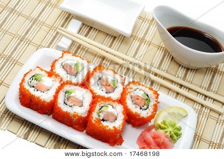 Rolls with Caviar serve with Soy Sauce and Chopsticks. Isolated on White Background