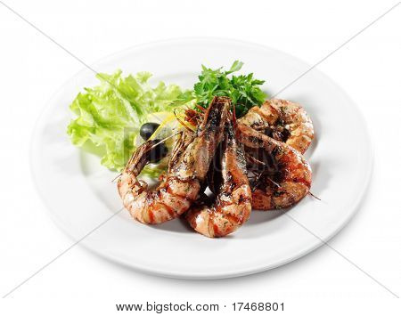 Seafood - Fried Shrimps Dressed with Salad Leaves, Parsley, Lemon and Olives. Isolated on White Background