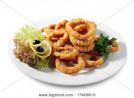 Meeresfrüchte - Fried Calamari. Frittierte Tintenfisch gekleidet mit Salat Blätter, Petersilie, Oliven und Zitronen. ISO