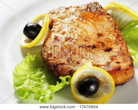 Fish Steak Served with Salad Leaves, Lemon and Olives. Isolated on White Background