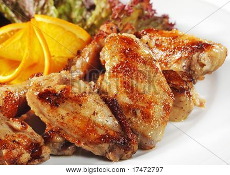 Fried Chicken Wings with Orange Slice and Vegetable Leaf