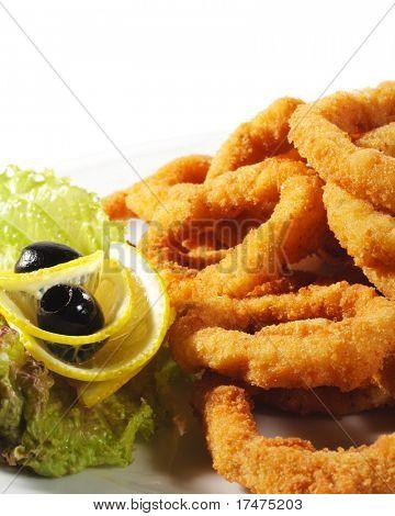 Seafood - Fried Calamari. Deep-fried Squid Dressed with Salad Leaves, Parsley, Olives and Lemon