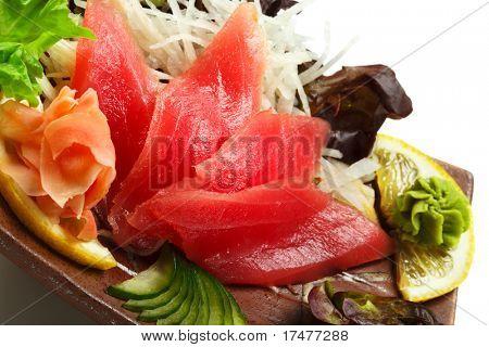 Thunfisch-Sashimi - Maguro (frische rohe Tuna) auf Daikon (weißer Rettich). Garniert mit Ingwer, Wasabi, Seaw