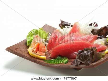 Tuna Sashimi - Maguro (fresh raw tuna) on Daikon (White Radish). Garnished with Ginger, Wasabi, Seaweed, Cucumber, Salad Leaf and Lemon