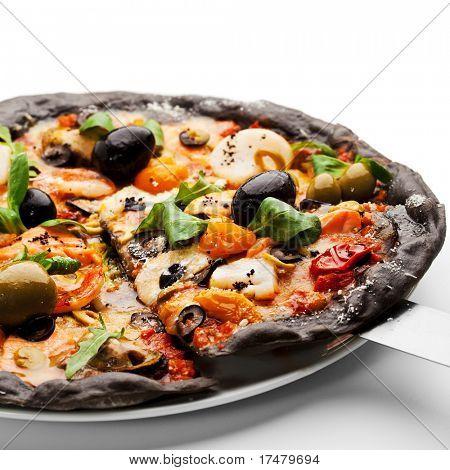 Pizza de masa de tinta negra con mariscos, aceitunas negras y verdes, tomate seco y hojas