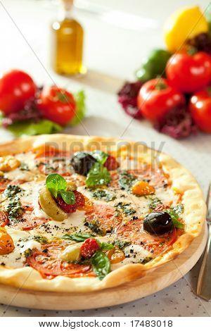 Pizza con queso Mozzarella, tomate y salsa Pesto. Sirve en la mesa de restaurante