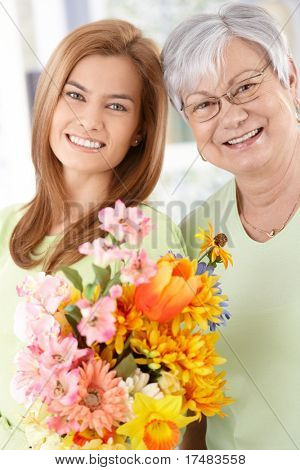 Senior mother and daughter smiling happily at Mother's day, having flowers.?