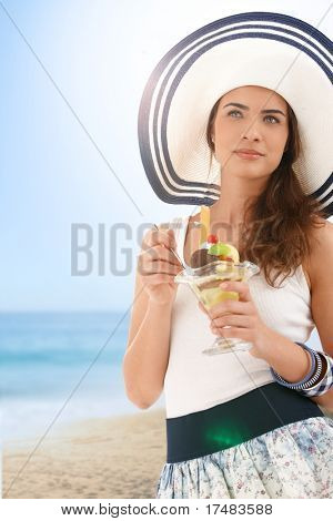 Attractive young woman in summer straw eating icecream on beach, looking away, smiling.?