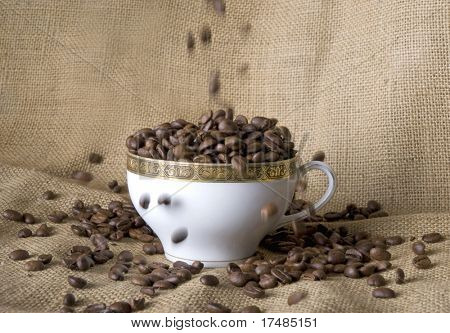 Coffee beans falling into a cup of coffee