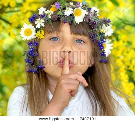 Small beautiful girl in wreath with a finger at her mouth