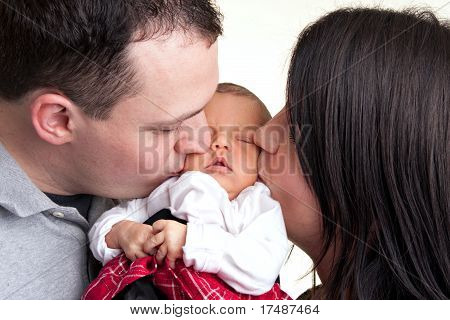 Happy Parents Kiss Their Newborn Baby