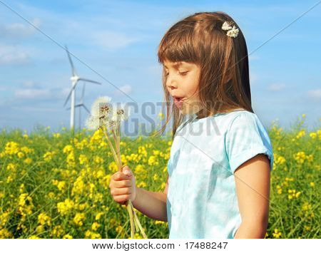Little girl in front of windmills blowing dandelions