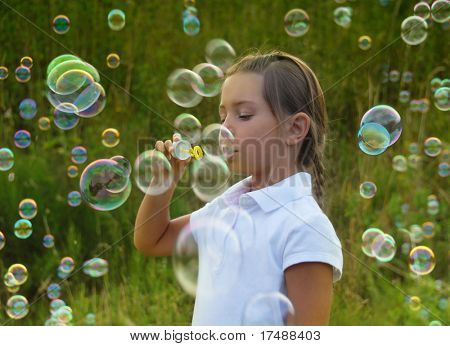 Little girl blowing soap bubbles at sunset