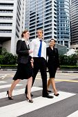 Three business people crossing road on zebra crossing