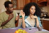 Sad African-american Male In Glasses Holding Hand On Chest, Apologizing To His Angry And Mad Wife, W poster