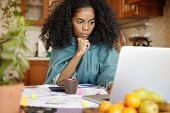 Serious Young African-american Female In Warm Wrap Working Through Finances At Night, Sitting At Kit poster