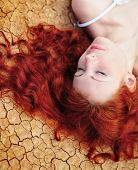 stock photo of red hair  - Beauutiful young woman with red hair on the dried up ground - JPG