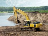 pic of land development  - The excavator works on coast of the river - JPG
