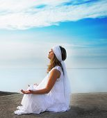stock photo of stress relief  - Young girl meditates on the beach - JPG