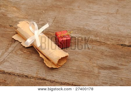 Red box with an old scroll on wooden background