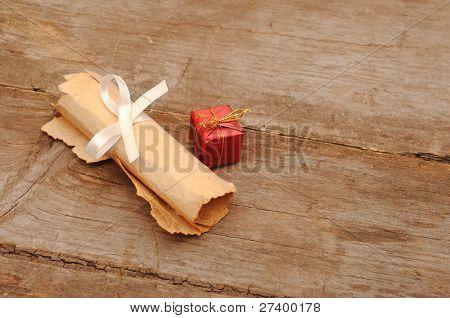 Caja roja con un viejo pergamino sobre fondo de madera