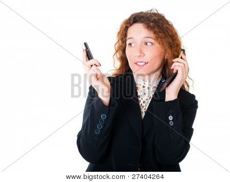 Young business woman with two mobile phones in talks. Isolated over white background.