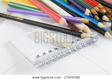 Multi-colored pencils and notepad on a white background