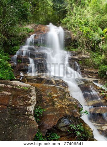 Waterfall And Green Leaves Of A Rainforest
