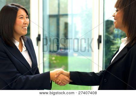 Mujeres empresarias estrechándole la mano