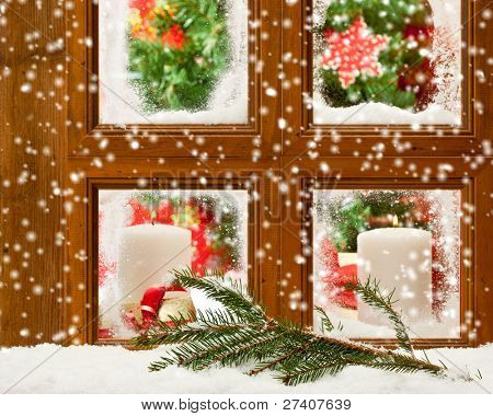 Candles at a festive seasonal window as snow falls onto a pine branch outside