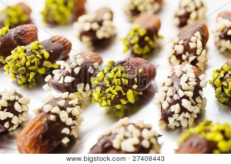 Dried dates with chocolate cover and almond and pistachio slivers on aluminum foil