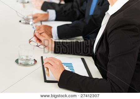 Business - people sitting in a meeting, close-up on hands and woman in the front