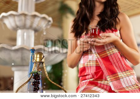 Wellness - young woman is relaxing in relaxation room with tea