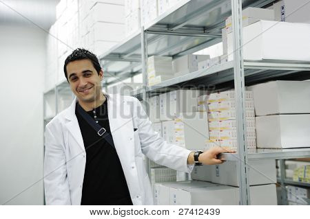 Young cheerful worker in modern drug warehouse