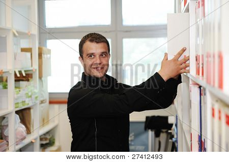 Man working at office putting folders together on shelves