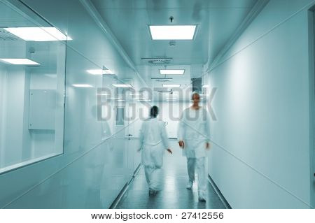 Modern bright factory interior with working people in motion