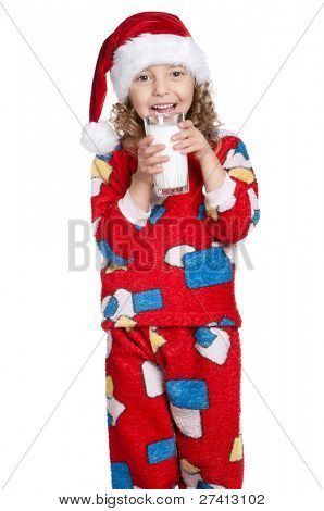 Portrait of happy little girl in pajamas and santa hat with glass of milk over white background